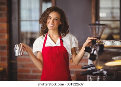 Portrait of a pretty waitress holding a jug at the coffee shop