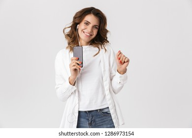 Portrait of pretty woman 30s using earphones and smartphone while standing isolated over white background