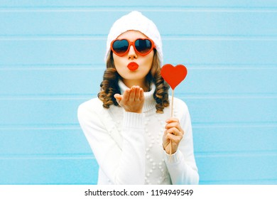 Portrait pretty woman blowing red lips sends air kiss with lollipop on stick heart shape in white knitted hat, sweater on blue background