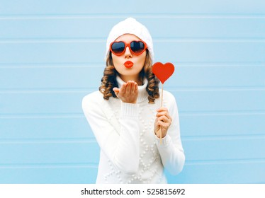 Portrait pretty woman blowing red lips sends air kiss holds lollipop heart shape white knitted hat, sweater over blue background