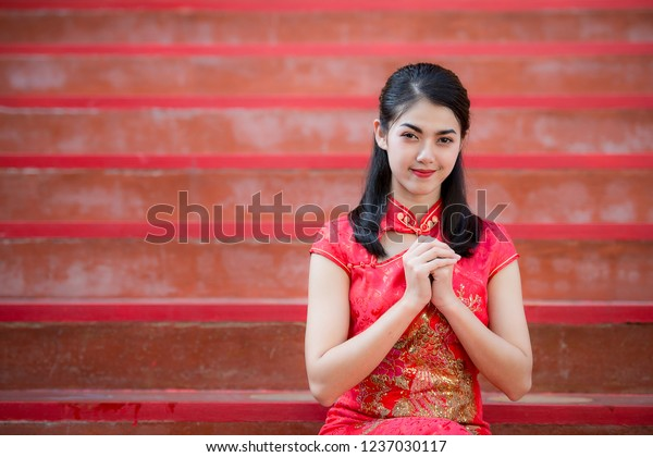 Portrait pretty woman in cheongsam red dress pay respect, in the Chinese New Year. Festivities, New Year Celebration