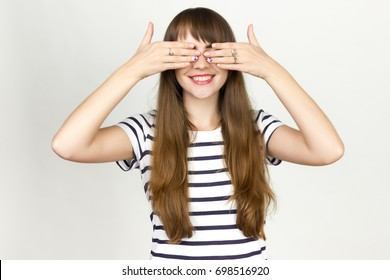 Portrait of a pretty woman  covering her eyes over gray background