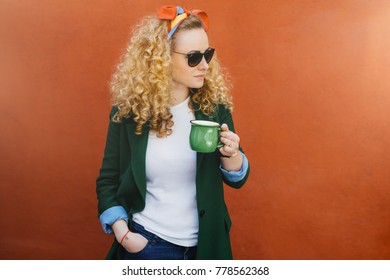 Portrait of pretty woman with curly hair wearing headband, stylish sunglasses and green jacket holding green cup of tea in one hand and other hand in pocket looking aside isolated over orange wall