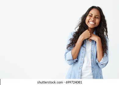 Portrait of pretty woman with dark clean skin and beautiful smile laughing out loud at funny joke while having fun indoors with friends, closing eyes in joy, looking carefree and relaxed.