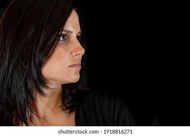 Portrait of pretty woman dark hair, brown eyes, dark background. Look to the side