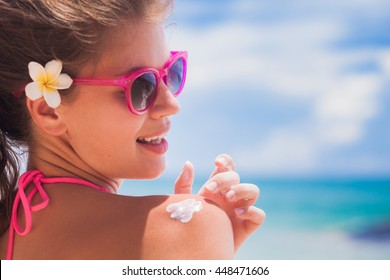 portrait of pretty woman with flower in her hair applying sunscreen on her shoulder, remote tropical beaches and countries. travel concept