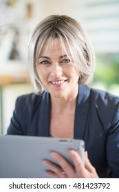 the portrait of a pretty woman of forty five years old with gray hairs who works in an office with a tablet. she is a business woman. she is smiling and looking at camera, she wears a blue jacket
