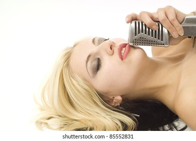 Portrait of pretty woman or girl music singer with microphone with eyes closed lying down on white