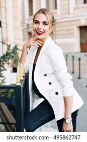 Portrait pretty woman leaning on fence on street. She wears white jacket,  has red lips, smiling to camera
