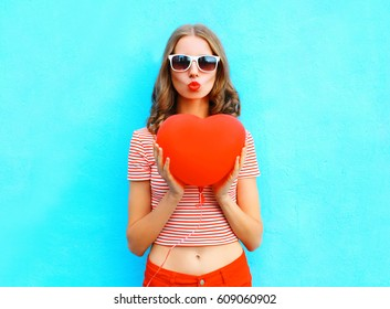 Portrait pretty woman making air kiss with red balloon heart shape over blue background