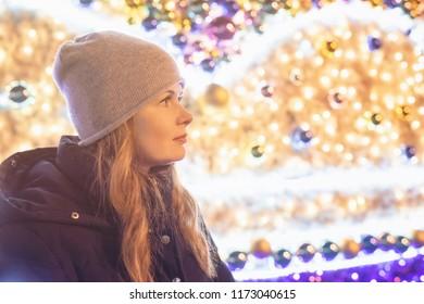 Portrait of pretty woman in the night fairies lights. Christmas fair