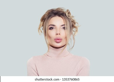 Portrait of pretty woman in pink turtleneck on white background. Model thinking, funny face