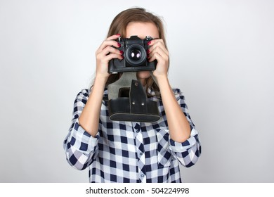 Portrait of a pretty woman  in plaid shirt holding an old camera in hands  making photostanding over gray background