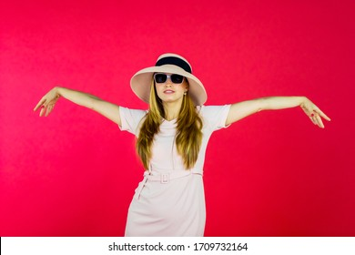 Portrait of pretty woman raising hands while wearing sunglasses and hat in the studio with red background