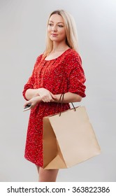 Portrait of pretty woman in red with shopping bag. Female model isolated studio background.