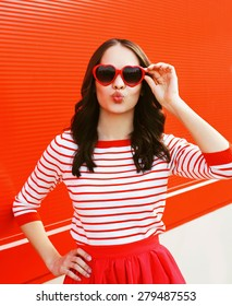 Portrait of pretty woman in red sunglasses blowing lips having fun outdoors