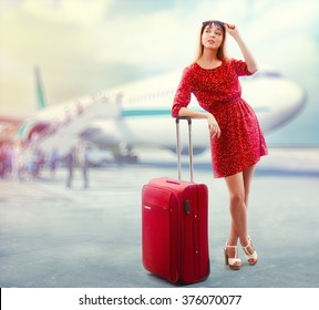 Portrait of pretty woman in red with travel bag boarding the plane.