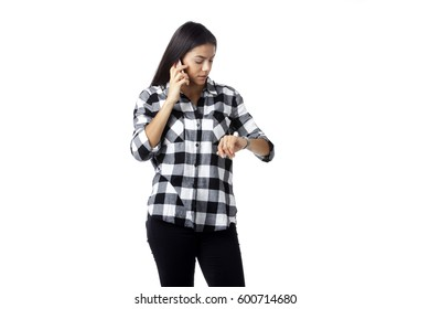 Portrait of a pretty woman speaking on cell phone and looking at her wristwatch. Isolated over white background
