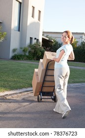 Portrait of an pretty woman with stack of box moving to a new house