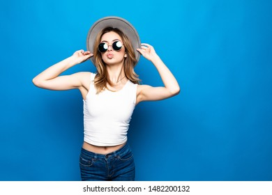 Portrait of pretty woman in sunglasses and hat over blue colorful