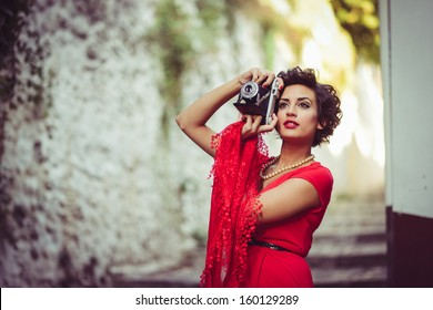 Portrait of a pretty woman, vintage style, in urban background, wearing a red dress taking photographs with a old camera