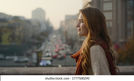 Portrait of pretty woman walking on city street. Closeup hipster girl smiling in urban background. Natural beauty woman enjoying day outdoors. Young woman walking in city