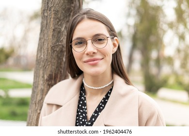 Portrait of a pretty woman wearing eyeglasses with a cute smile standing in the park, close up vertical