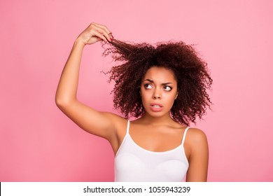 Portrait of pretty, worry, attractive girl examine, look her curly hair, holding strand with hand, she want straight perfect, soft, shine hair, need treatment and therapy  isolated on pink background