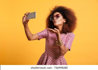Portrait of a pretty young afro american woman in retro style clothes sending air kiss while standing and taking a selfie isolated over yellow background
