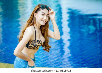 portrait Pretty young asian fashion sexy woman in sunglasses posing on swimming pool  in summer .