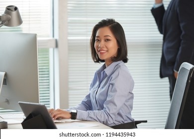 Portrait of pretty young Asian female entrepreneur working on computer at her ofice table