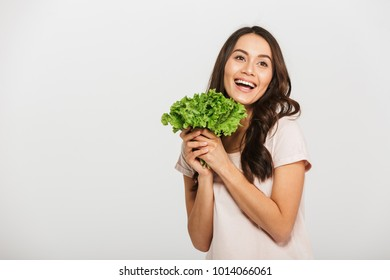 Portrait of a pretty young asian woman holding lettuce and laughing isolated over white background