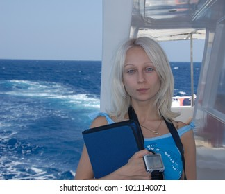 A portrait of a pretty young blonde girl or woman with blue eyes in front of a blue sea. A girl is a scuba diving student, she stands on a diver's yacht and holds a logbook and a dive watch