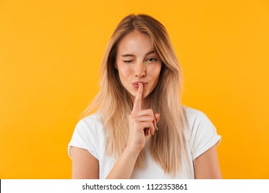 Portrait of a pretty young blonde girl showing silence gesture and winking isolated over yellow background