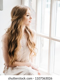 Portrait of pretty young bride with beautiful hairstyle and makeup looking at window