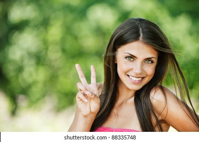 portrait pretty young brunette smiling shows victory sign background summer green park