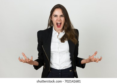 Portrait of a pretty young businesswoman screaming spreads her hands on the sides and crooked fingers and  standing over gray background
