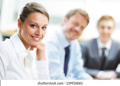 Portrait of a pretty young businesswoman smiling in a meeting with her colleagues in background