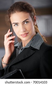 Portrait of pretty young businesswoman talking on mobile smiling.?