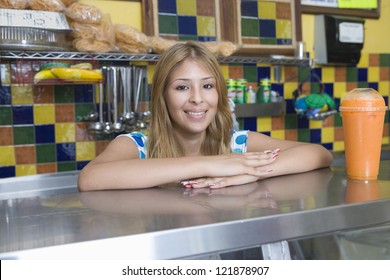 Portrait of pretty young Caucasian female standing counter of a diner