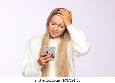 Portrait of pretty young European sad and disappointed female, received bad news and looking at phone, hand on forehead/ Emotions and awkwardness gestures concept/ Epic fail, facepalm, life situations