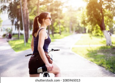 Portrait of pretty young female riding on her bicycle looking away smiling, with sun flare. Woman cycling on a summer day.