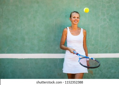 Portrait of a pretty, young, female tennis player in front of a training wall on a tennis court