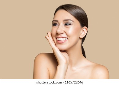 Portrait of pretty young girl and bare shoulders, touching her cheek, looking away and smiling, on beige background