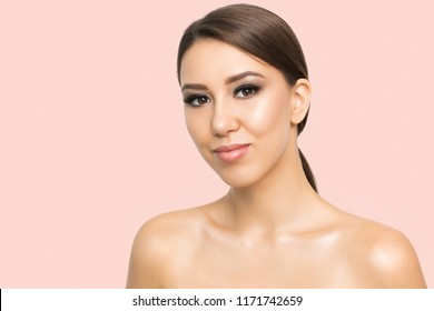 Portrait of pretty young girl and bare shoulders, looking at camera with tender smile, on light pink background
