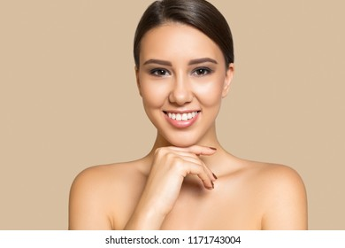 Portrait of pretty young girl and bare shoulders, looking at camera and smiling, on beige background