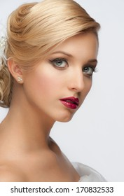 Portrait of a pretty young girl with a beautiful vintage hairstyle and makeup, wedding style