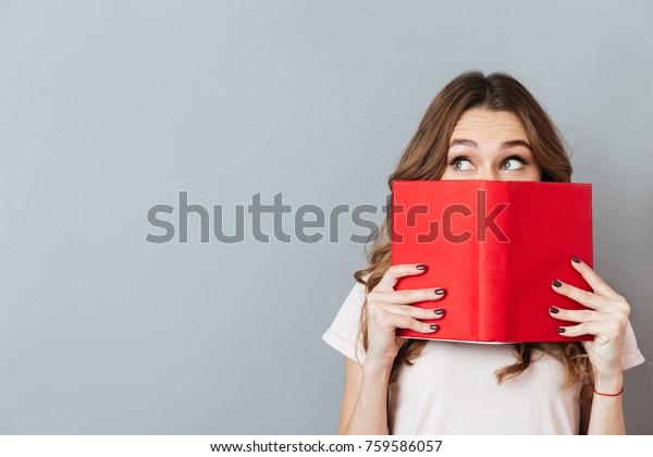 Retrato de una niña linda escondida detrás de un libro abierto y mirando lejos aislada sobre fondo gris de pared