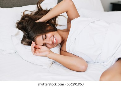Portrait pretty young girl on bed in modern apartment in the morning. She keeps eyes closed and looks satisfied