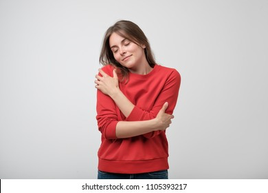Portrait of a pretty young girl in red shirt hugging herself. Concept of selfish emotion.